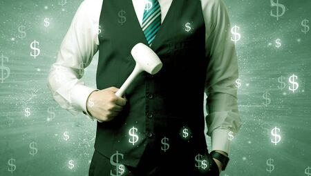 Handsome businessman holding tool with dollar symbols around and with green background Stock Photo