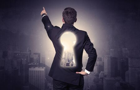multiple choice: Young businessman standing and thinking with keyhole on his back and city graphic around