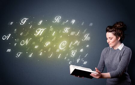 Casual young woman holding book with shiny letters flying out of it photo