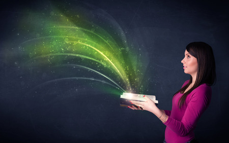 Casual young woman holding book with green wave flying out of it photo