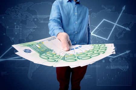 stash: Young businessman holding large amount of bills with blue charts in the background