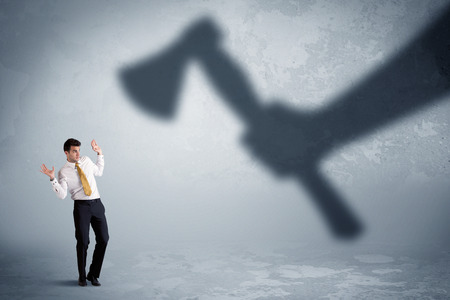 Businessman afraid of a huge shadow hand holding an axe concept on background Stock Photo