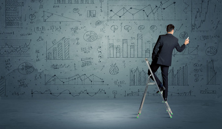 interval: A businessman in modern stylish elegant suit standing on a small ladder and drawing pie and block charts on grey wall background with exponential progressing curves, lines, circles, angles, blocks, numbers Stock Photo