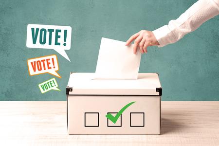 A hand placing a voting slip into a ballot box Foto de archivo