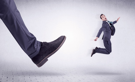 Small young businessman kicked out by a big black shoe Stock Photo