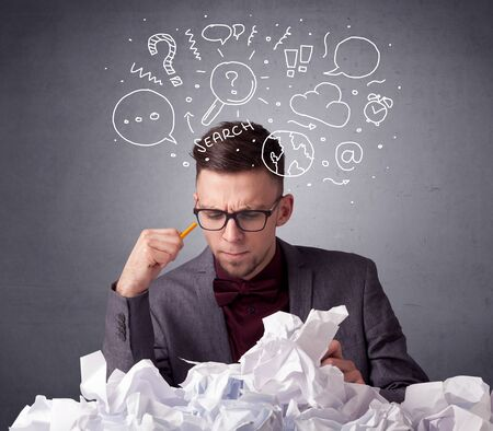 smart man: Young businessman sitting behind crumpled paper with mixed doodles over his head Stock Photo