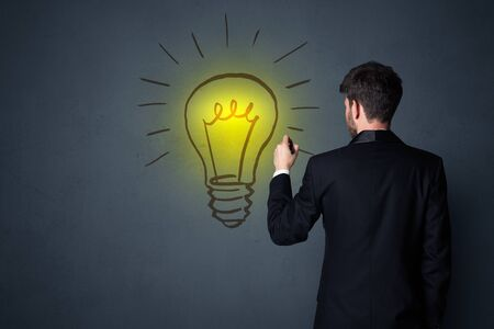 smart man: Young businessman in black suit standing in front of a drawn yellow lightbulb