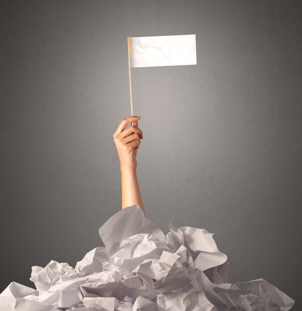 difficulties: Female hand emerging from crumpled paper pile holding a white blank flag Stock Photo