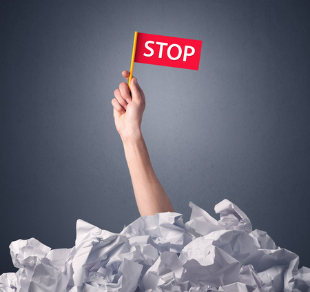 difficulties: Female hand emerging from crumpled paper pile holding a red flag with stop written on it Stock Photo