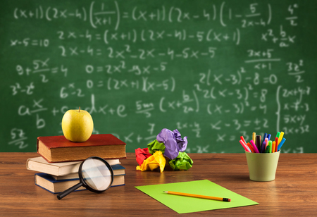 Back to school concept with long numbers calculation on blackboard and a desk with books, fruit