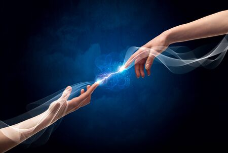 two generation family: Two male arms reaching for each other, with a smoking electric current connecting their fingers in empty space background concept Stock Photo