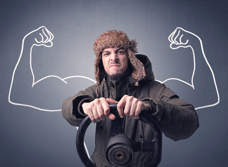 Young man holding black steering wheel with muscly arms drawn next to him Stok Fotoğraf