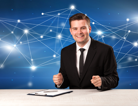 reason: Young handsome businessman sitting at a desk with a blue connection graphic behnid him Stock Photo