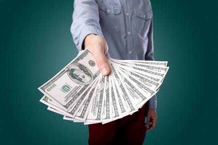 stash: Young businessman holding large amount of bills Stock Photo