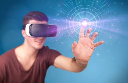 eyewear: Young impressed man wearing virtual reality goggles with blue circles around his finger Stock Photo