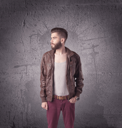 funny bearded man: A hipster fashion model guy in casual clothing stnading with mobile phone in front of concrete urban wall background concept