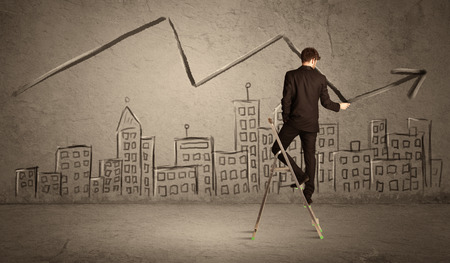 exponential: A man in elegant suit standing on a small ladder and drawing a line on brown wall background with buildings Stock Photo