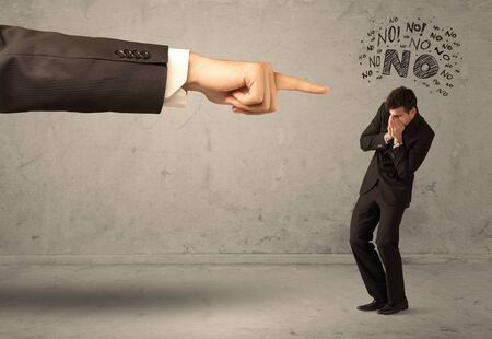 disagreeing: A young employee disagreeing and arguing with boss, feeling ashamed concept. A large hand pointing at businessman saying no