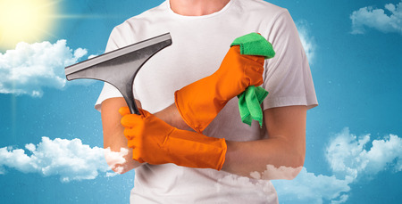Sunny and cloudy concept with male housekeeper and orange gloves on his hand