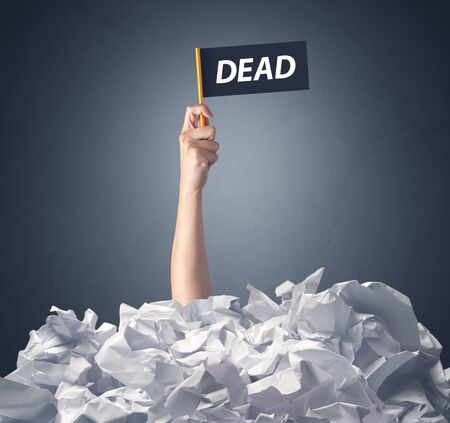 Female hand emerging from crumpled paper pile holding a black flag with dead written on it Stock Photo