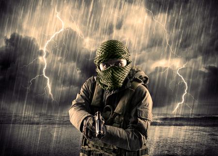 Portret van een gevaarlijke gewapende terrorist met masker en pistool in een onweersbui met bliksem Stockfoto