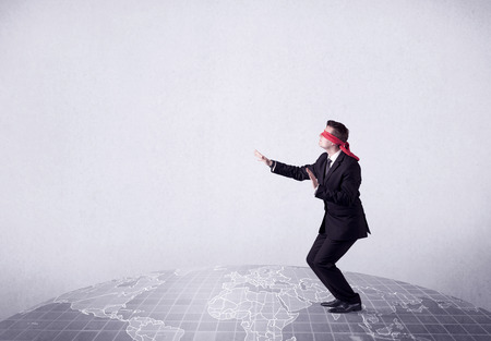 Young blindfolded businessman steps on a grey world map