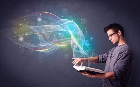 Casual young man holding book with rainbow waves flying out of it photo