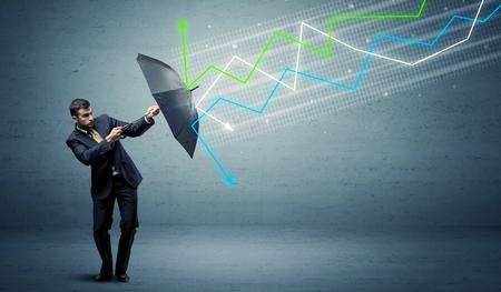 persona de negocios con el paraguas y flechas de colores en el mercado de valores concepto de Foto de archivo