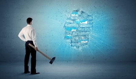 Bedrijfsmens die grungy bakstenen muur met reusachtige hamer raken