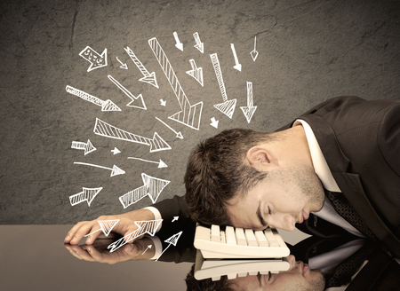 fed up: An exhausted business person resting his head on keyboard with pressure illustrated by arrows pointing at him concept Stock Photo