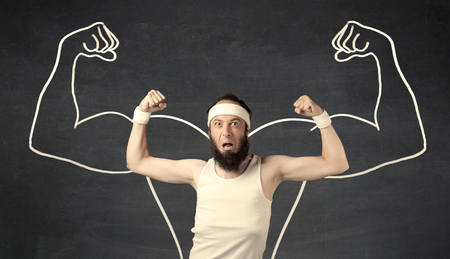 A young male with beard and glasses posing in front of grey background, thinking about lifting weight with big muscles, illustrated by white drawing concept. photo
