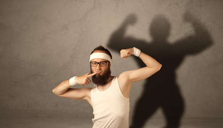 A funny young guy posing in front of brown background with musculous body shadow reflected on the wall photo