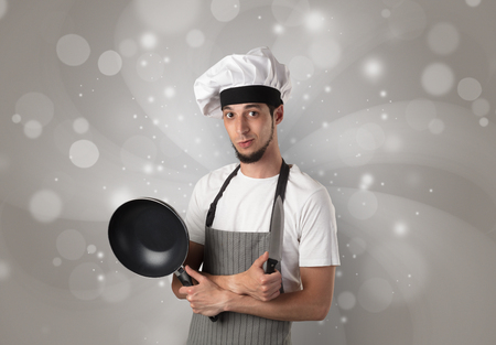 Male cook with kitchen tools and shiny grey wallpaper Stock Photo