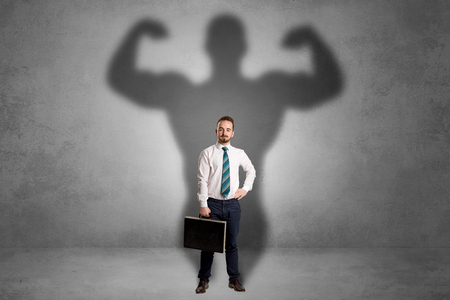 better: Lovely serious businessman standing with a muscular powerful shadow behind his back Stock Photo