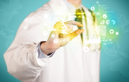 A doctor in white coat with a stethoscope on one shoulder holding a pill with green glowing graphs, lines, numbers, charts, between his fingers Stock Photo