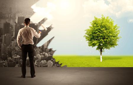 Zakenman in elegant kostuum die zich met zijn rug bevinden, een rol houden en het grijze stadslandschap in groene boom in het heldere concept van de aardmilieu transformeren