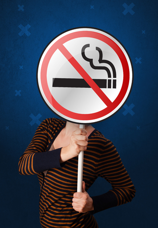 warned: Casual young woman holding round sign with no smoking graphic Stock Photo