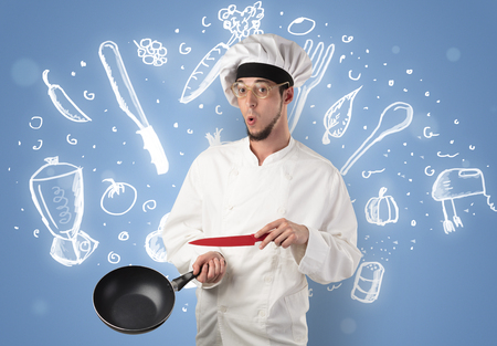 Young cook with kitchen instruments and drawn recipe concept on wallpaper Stock Photo