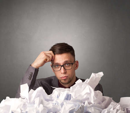difficulties: Young businessman sitting behind crumpled paper with grey background Stock Photo