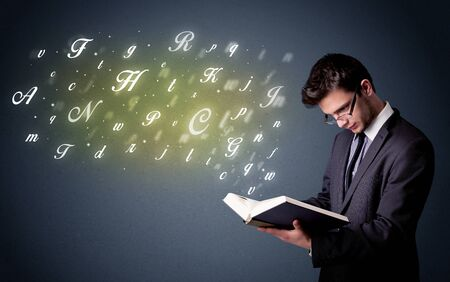 Casual young man holding book with shiny letters flying out of it photo