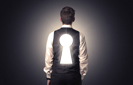 leadership key: Young businessman standing and thinking with black keyhole on his back