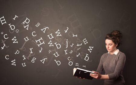 Casual young woman holding book with white alphabet flying out of it photo