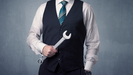 darn: Young, handsome, cute businessman holding tool with grey background
