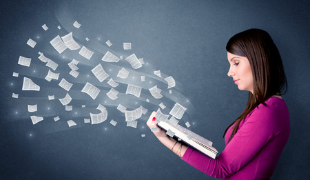 Casual young woman holding book with pages flying out of it photo