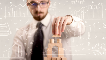 Young handsome businessman using wooden building blocks with white calculations scribbled around him photo