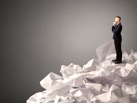 Thoughtful young businessman standing on a pile of crumpled paper with a deep grey background photo