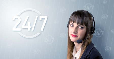 Young female telemarketer with a 247 sign next to her