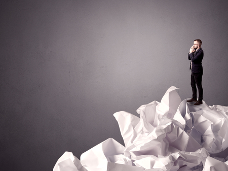 Thoughtful young businessman standing on a pile of crumpled paper with a grungy grey background photo