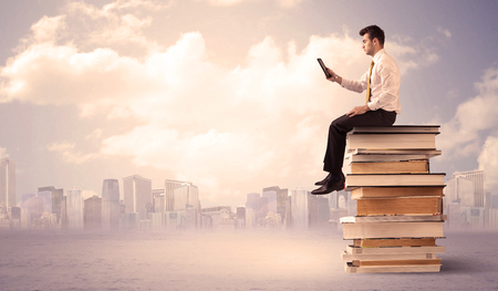 diligente: A serious student with laptop tablet in elegant suit sitting on a stack of books in front of cityscape with clouds