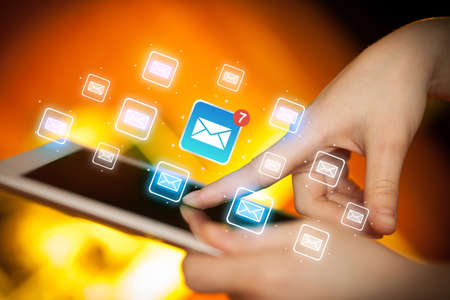 Female hands touching tablet with e-mail icons Stock Photo